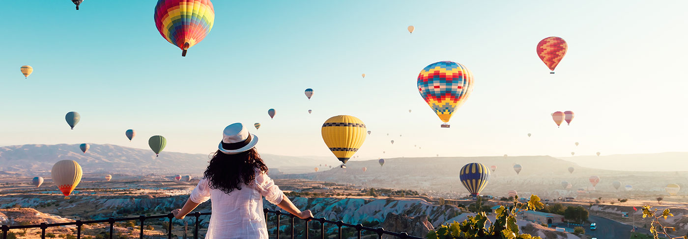 A woman watches multicolored hot air balloons rise over a canyon.