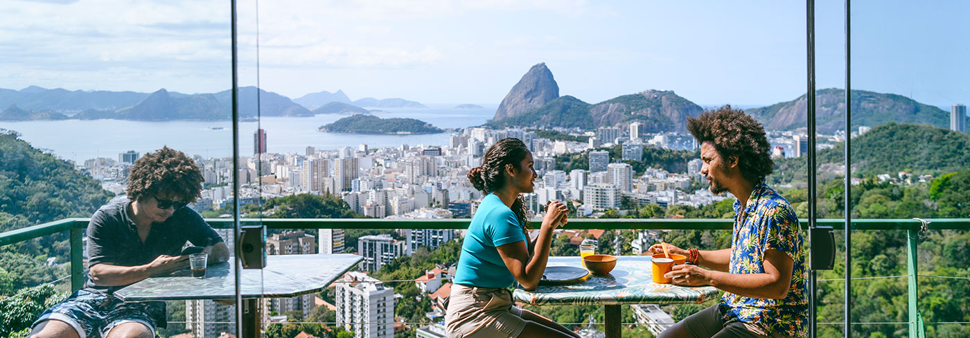 A couple eat on a cafe terrace overlooking Sugarloaf Mountain in Rio de Janeiro.